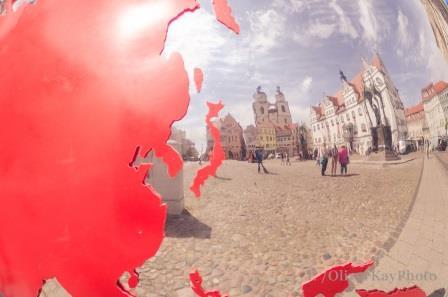 Weltkugel auf dem Marktplatz mit Stadtkirche im Spiegel